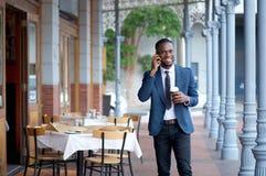 Дружелюбный бизнесмен идя и говоря на мобильном телефоне Стоковые Фото