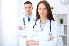 Дружелюбный женский доктор на предпосылке мужского врача в офисе больницы Стоковые Фото