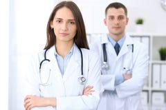 Дружелюбный женский доктор на предпосылке мужского врача в офисе больницы Стоковые Изображения RF