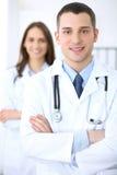Дружелюбный мужской доктор на предпосылке женского врача в офисе больницы Стоковое Изображение RF