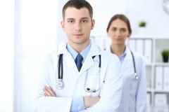 Дружелюбный мужской доктор на предпосылке женского врача в офисе больницы Стоковые Изображения RF