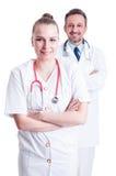 Дружелюбный мужчина и женские доктора с стетоскопами и белым coa Стоковые Фотографии RF