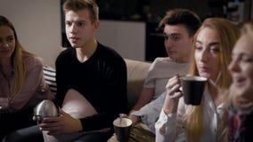 5 друзей смотрят фильмы ТВ сидя на софе в живя комнате в вечере праздников, выпивая чае и кофе акции видеоматериалы