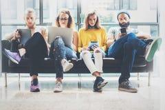 Друзья битников группы взрослые сидя софа используя современные устройства Концепция сыгранности приятельства запуска дела творче стоковое фото