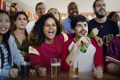 Друзья веселя спорт на баре совместно стоковое фото