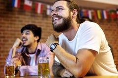 Друзья веселя спорт на баре совместно стоковая фотография