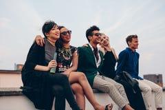 Друзья вися вне совместно на крыше Стоковые Фотографии RF