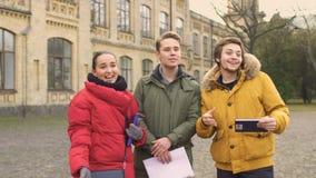 Друзья встречают их друга стоя близко университет акции видеоматериалы