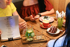 Друзья встречи в кафах и пироге вишни кондитерскаи заказа, mer Стоковое Фото