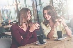 Друзья встречи в кафе 2 жизнерадостных девушки сидят на таблице, выпивают кофе и обсуждают новости Стоковые Изображения RF