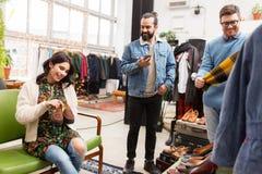 Друзья выбирая одежды на винтажном магазине одежды стоковое фото rf