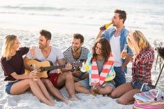 Друзья выпивая пиво на пляже стоковое фото rf