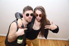 Друзья выпивая спирт от бутылки и представляя на партии стоковое изображение rf