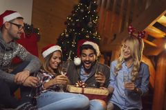 Друзья выпивая шампанское и раскрывая настоящие моменты на Рожденственской ночи стоковое изображение rf