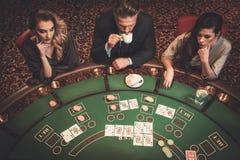 Друзья высшего класса играя в азартные игры в казино Стоковые Изображения RF