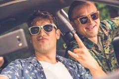 Друзья в автомобиле подготавливая для отключения каникул дороги и принимая автопортрет путем использование мобильного телефона стоковое фото