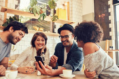 Друзья в кафе смотря фото на мобильном телефоне Стоковое Фото