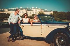 Друзья в классическом автомобиле с откидным верхом стоковые изображения