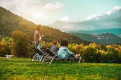 Друзья в луге осени наслаждаясь пейзажем Стоковые Фотографии RF