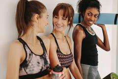 Друзья в спортзале беседуя после разминки Стоковое Изображение RF