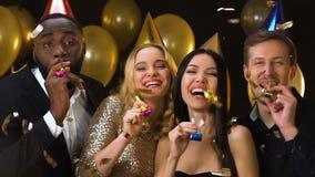 Друзья в шляпах дня рождения с воздуходувками партии стоя под падая confetti сток-видео