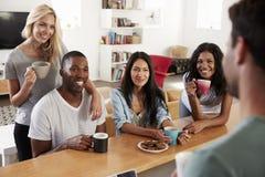 Друзья говоря и выпивая кофе в современной кухне Стоковые Изображения