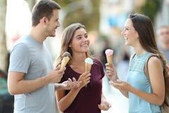 Друзья говоря и есть мороженое в улице Стоковые Изображения