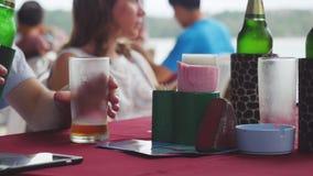 Друзья говоря пиво питья и смеясь над на ресторане около seashore Стоковые Изображения RF
