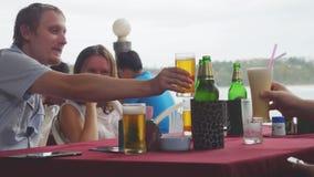 Друзья говоря пиво питья и смеясь над на ресторане около seashore Стоковая Фотография