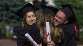 Друзья градуируют в академичных платьях поздравляя и обнимая один другого сток-видео