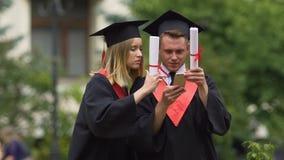Друзья градуируют нося академичные платья осматривая фото на smartphone сток-видео