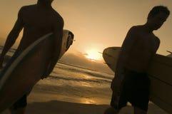 Друзья гуляя на пляж на заходе солнца Стоковое Изображение