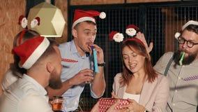 Друзья дают подарок для женщины, закрывая ее глаза руками на рождественской вечеринке видеоматериал