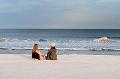 Друзья 2 девушки смотря на море на пляже в осени Стоковые Изображения