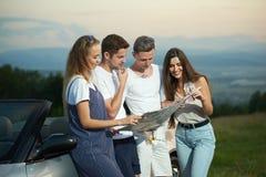 Друзья держа карту и планируя путешествие cabriolet стоковые фото