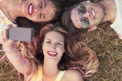Друзья лежа на траве и принимая selfie Стоковое фото RF