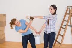 Друзья держа кисти и могут в новом доме Стоковое фото RF