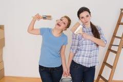 Друзья держа кисти и могут в новом доме Стоковые Фото
