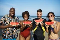 Друзья есть арбуз на пляже стоковое фото