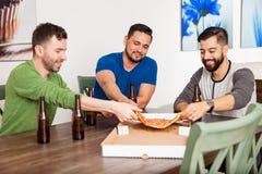 Друзья есть пиццу и выпивая пиво Стоковое фото RF