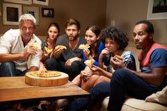 Друзья есть пиццу на приеме гостей, смотря телевидение стоковые фото