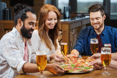 Друзья есть пиццу с пивом на ресторане Стоковое фото RF