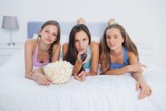 Друзья есть попкорн и смотря ТВ Стоковое фото RF