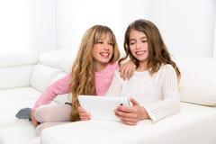 Друзья детей ягнятся девушки играя вместе с ПК таблетки Стоковые Изображения