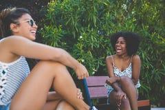 Друзья детенышей довольно женские сидя на смеяться над стенда Стоковая Фотография