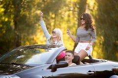 Друзья ехать автомобиль с откидным верхом Стоковое Изображение RF