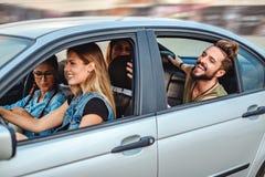 Друзья ехать в автомобиле с открытыми окнами и смеяться над Стоковые Изображения RF