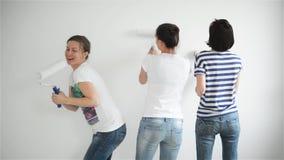Друзья делают ремонты дома Смешные девушки танцуют и красят стены в квартире видеоматериал