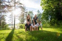 Друзья делая человеческую пирамиду на травянистом поле Стоковые Изображения RF