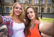 Друзья делая selfie и имея потеху в парке Счастливые девочка-подростки тратят время совместно в городе Стоковые Фотографии RF